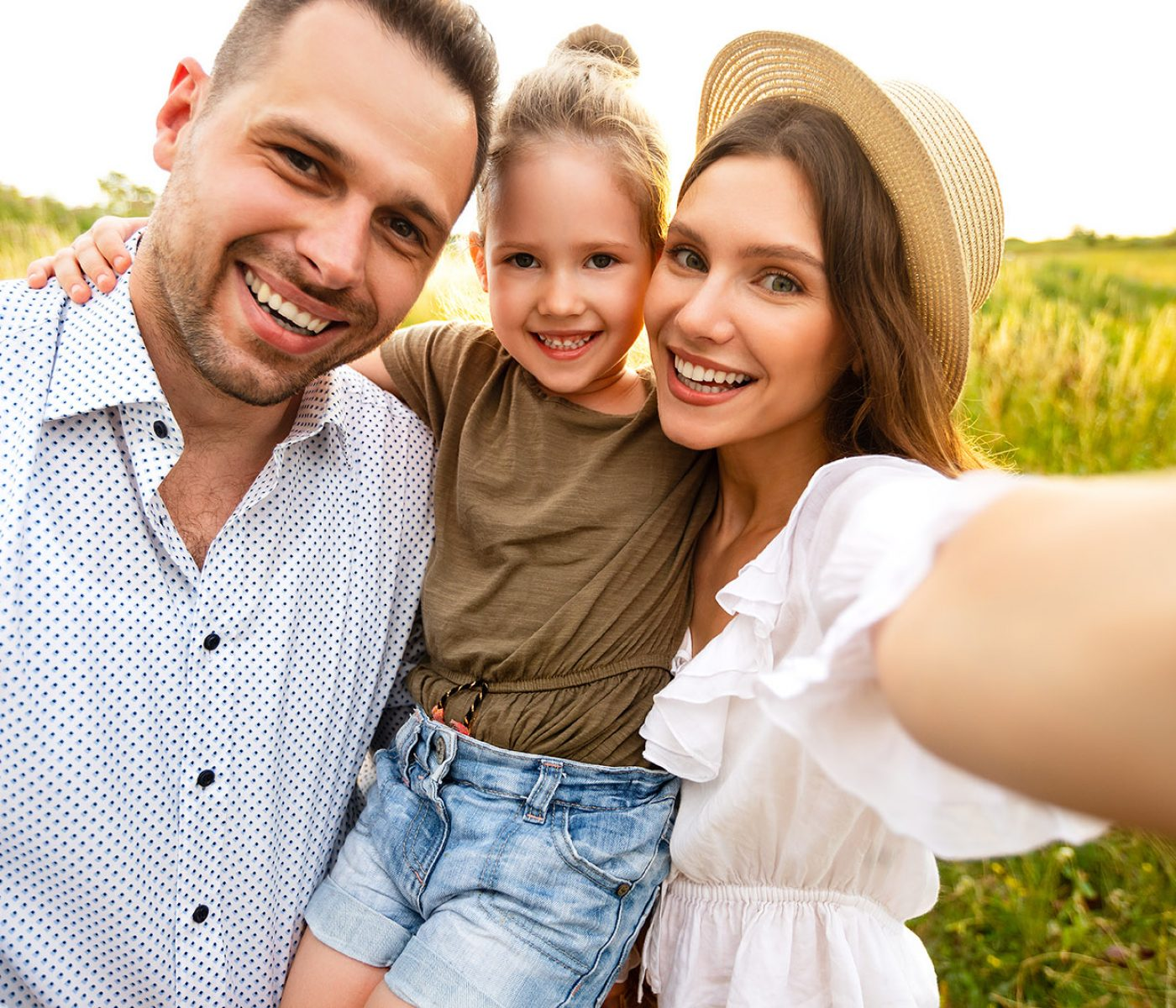 Family Portrait. Closeup of adorable couple with cute kid taking selfie, having fun outdoors